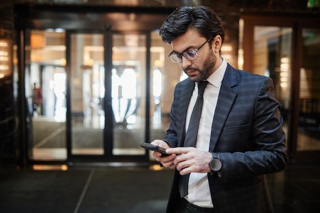 호텔 로비에 서 있는 동안 스마트폰을 사용하는 성공적인 중동 사업가의 허리 초상화, 복사 공간