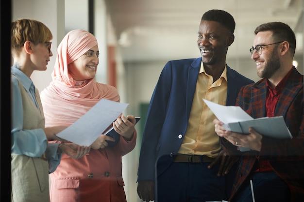 成功した多民族のビジネスチームがお互いに話し、オフィスのインテリアに立っている間笑顔の肖像画を腰に当てる
