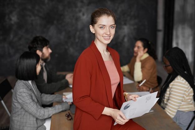 Талия вверх портрет успешной молодой бизнес-леди в красной куртке и улыбающейся в камеру с разнообразной группой людей, встречающихся в фоновом режиме, копией пространства