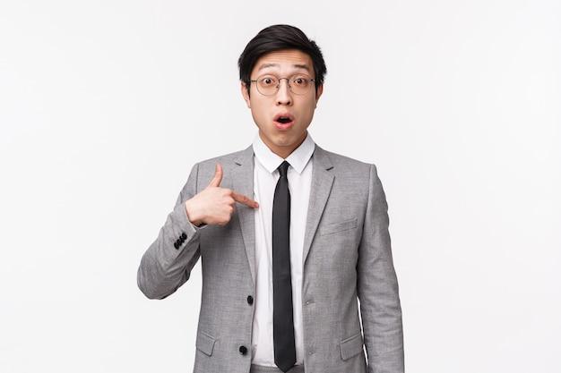 Портрет талии вверх удивленного и смущенного азиатского бизнесмена, офисного работника, указывающего на себя с недоверием и озадаченным выражением, будучи выбранным или упомянутым, стоя на белой стене