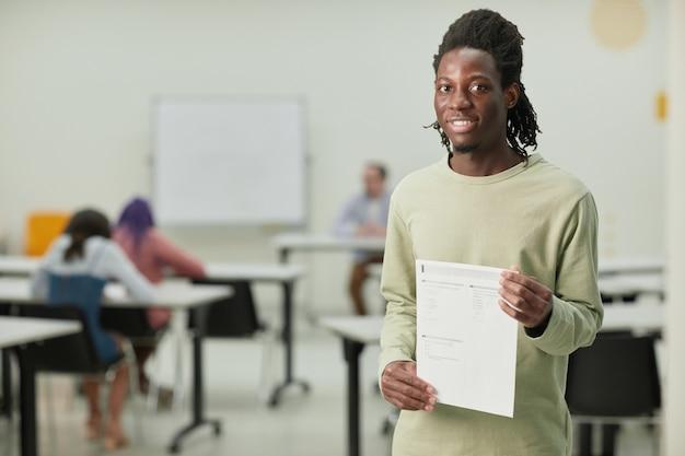 Талия вверх портрет афроамериканского мальчика-подростка в школьном классе, счастливо улыбающегося в камеру и держащего свидетельство об испытании, копировальное пространство