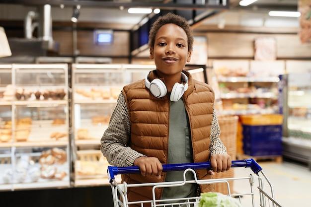 Подняв талию портрет афроамериканского мальчика-подростка, толкающего тележку с продуктами в супермаркете и улыбающегося в камеру, скопируйте пространство