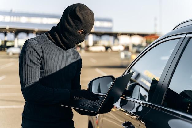 낮에 차 근처에 서 있는 동안 노트북 해킹 경보 시스템이 있는 자동차 도둑의 허리 초상화. 스톡 사진