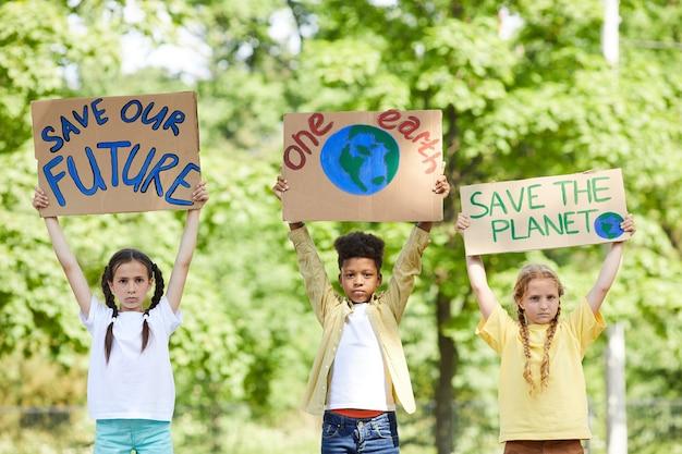 야외에서 자연을 위해 항의하면서 save planet save future 표지판을 들고 세 어린이의 초상화를 허리 위로 올리십시오.