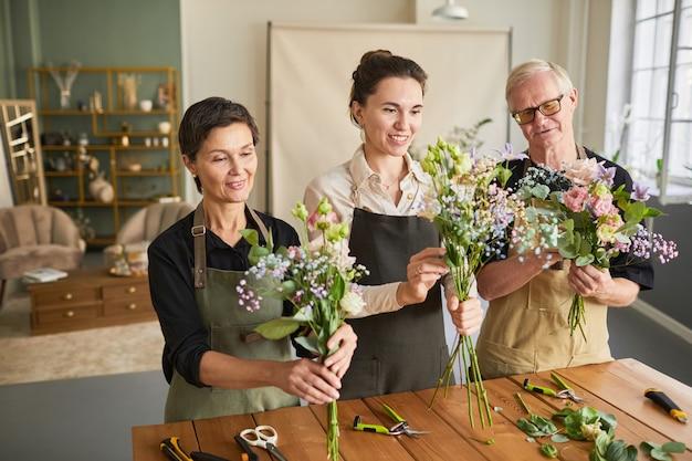 아늑한 작업실에서 일하는 동안 꽃 작곡을 하는 세 플로리스트의 허리 위 초상화