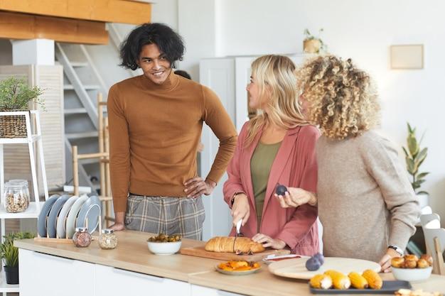 屋内でディナーパーティーのために料理をしながら楽しくおしゃべりしている3人の友人の肖像画を腰に当ててください。