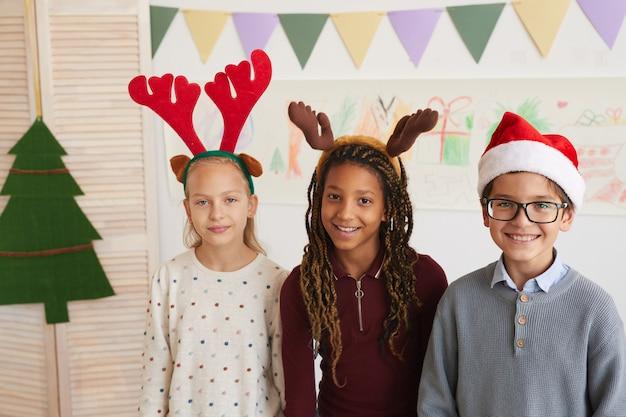 クリスマスの授業を楽しみながら、サンタの帽子をかぶってカメラを見ている3人の子供の肖像画を腰に当て、スペースをコピー