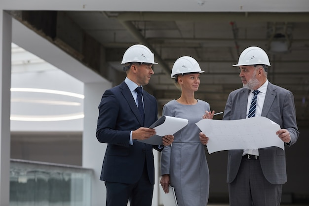 안전모를 착용하고 실내에서 건설 현장을 검사하는 동안 계획을 잡고있는 세 명의 성공적인 비즈니스 사람들의 초상화를 허리 위로 올리고,