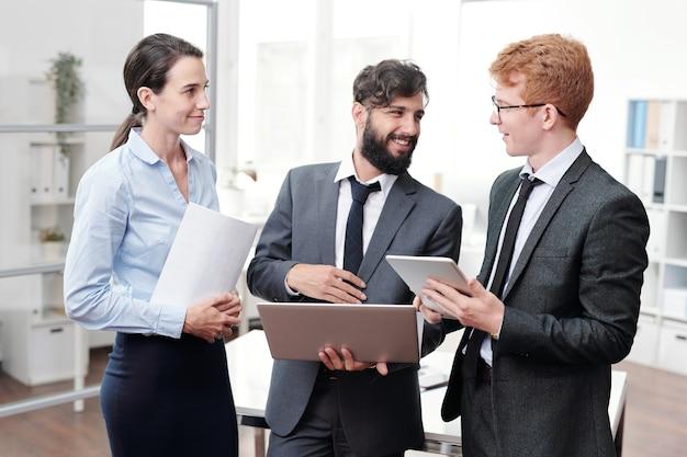 Портрет трех молодых деловых людей, обсуждающих работу и улыбающихся, стоя в современном офисе, с копией пространства
