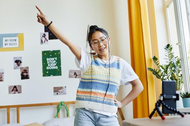 Портрет модной девочки-подростка, танцующей под камеру, во время съемок видео в интерьере уютной комнаты