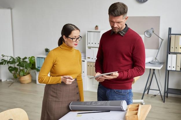 사무실에서 청사진을 함께 작업하는 동안 디지털 태블릿을 사용하는 두 건축가의 초상화를 허리 위로 올리고,