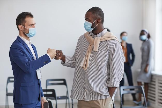 ビジネス会議での休憩中に非接触の挨拶としてマスクを着用し、拳をぶつける2人のビジネスマンの肖像画を腰に当て、スペースをコピーします