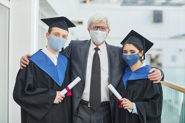 Портрет двух выпускников колледжа в масках, позирующих со зрелым профессором в помещении