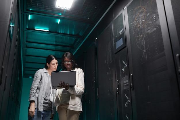 Портрет двух ит-инженеров женского пола, настраивающих серверную сеть через ноутбук во время работы в центре обработки данных, место для копирования