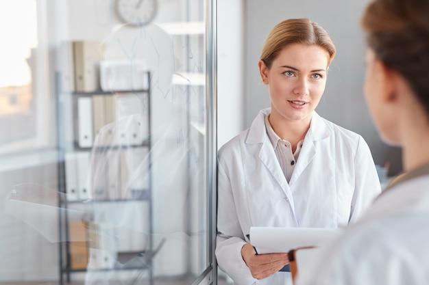 의료 실험실에서 연구를하는 동안 이야기하고 클립 보드를 들고 두 여성 과학자의 초상화를 허리, 복사 공간