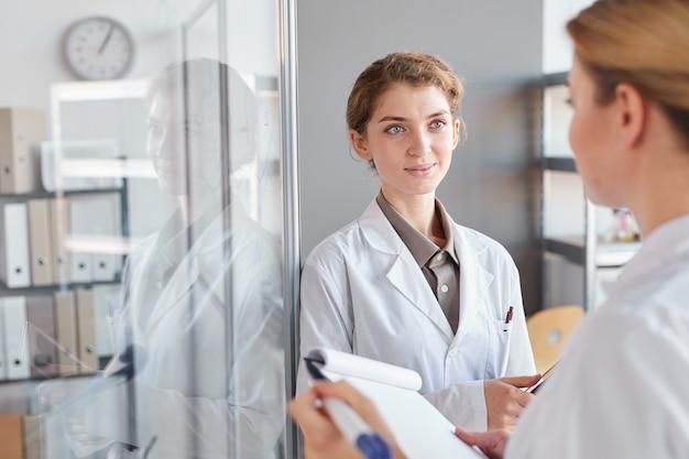 의료 실험실에서 연구를하는 동안 유리 벽에 쓰고 클립 보드를 들고 두 여성 과학자의 초상화를 허리, 복사 공간