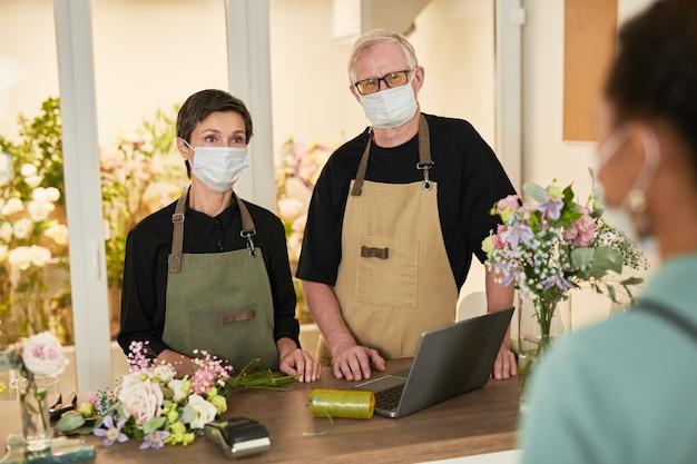 Портрет двух флористов в масках, разговаривающих с покупателем в копировальном пространстве цветочного магазина