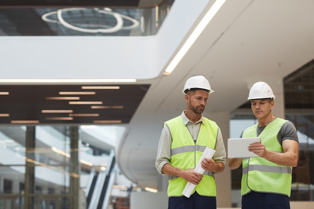 Портрет двух зрелых строительных подрядчиков, использующих цифровой планшет, стоя в офисном здании на строительной площадке