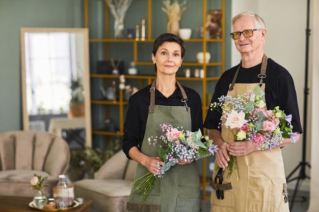 Портрет двух зрелых флористов с букетом, стоящих в цветочном магазине и глядя на ...