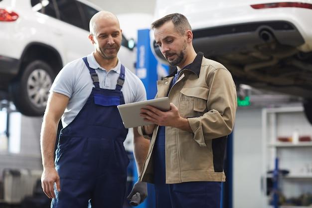 Портрет двух современных автомехаников, использующих цифровой планшет, стоя в автомагазине, с копией пространства