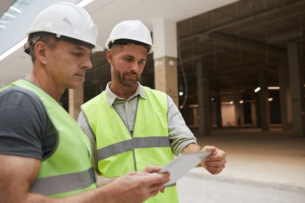 Портрет двух профессиональных строительных подрядчиков с помощью цифрового планшета, стоя на строительной площадке
