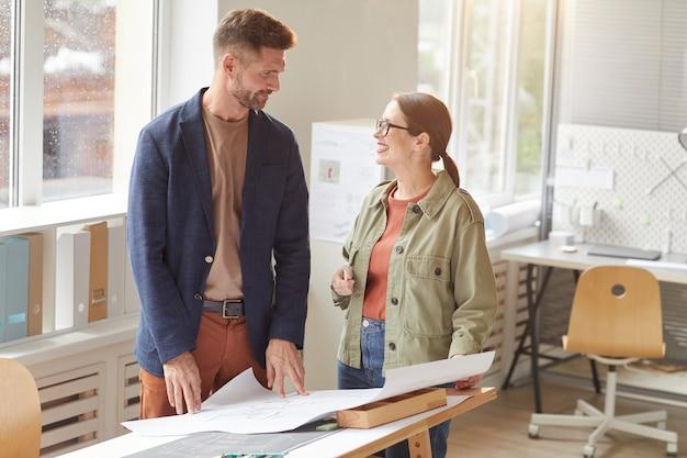 Подняв талию портрет двух улыбающихся архитекторов, обсуждающих чертежи, стоя у чертежного стола в офисе,