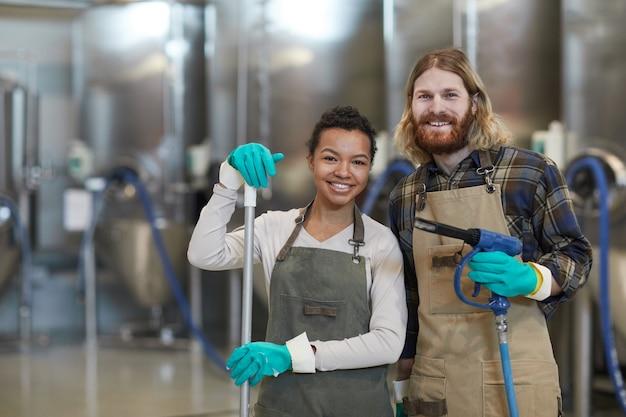 Поднимите талию портрет двух улыбающихся молодых людей в фартуках и смотрящих в камеру во время уборки на промышленном заводе, копировальное пространство