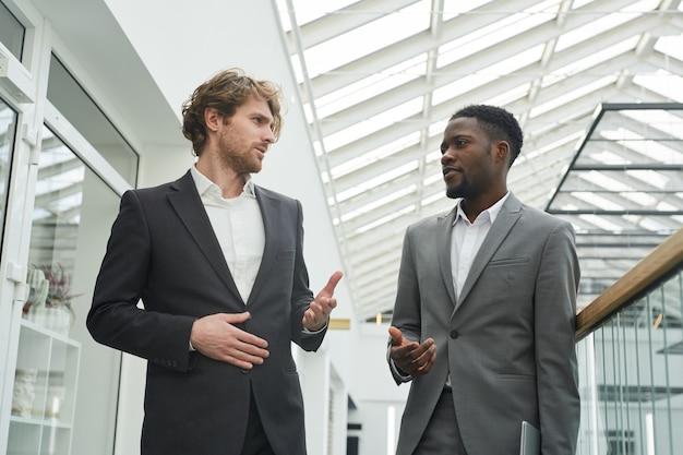 Портрет двух успешных бизнесменов в костюмах, беседующих с камерой в современном интерьере офисного здания