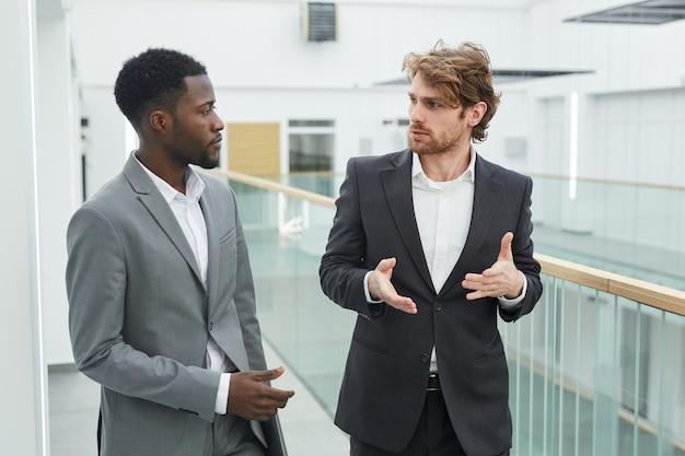 Портрет двух успешных бизнесменов в костюмах в чате, идущих к камере в современном интерьере офисного здания