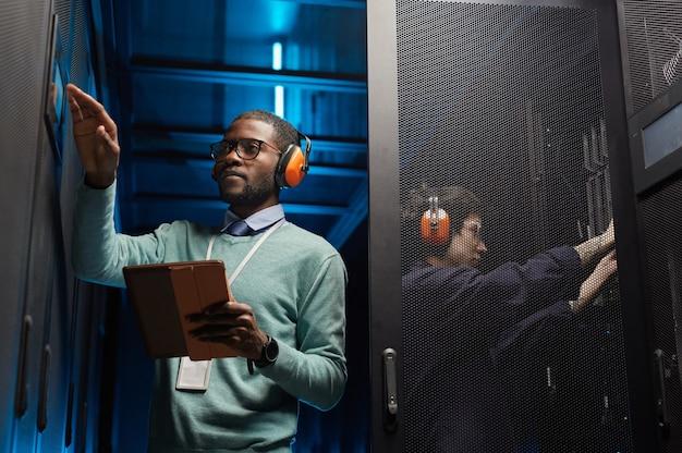 Портрет двух технических специалистов, настраивающих компьютерную сеть во время работы в центре обработки данных