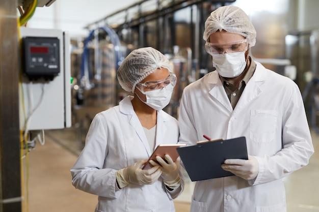 화학 공장, 복사 공간에서 생산에 대해 논의하는 동안 마스크와 실험실 가운을 입은 두 작업자의 허리 초상화