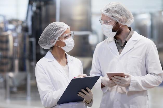 현대 화학 공장에서 생산에 대해 논의하는 동안 보호복을 입은 두 노동자의 허리 위 초상화