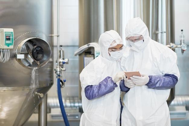화학 공장에서 디지털 태블릿을 사용하는 동안 보호복을 입은 두 작업자의 허리 초상화, 복사 공간