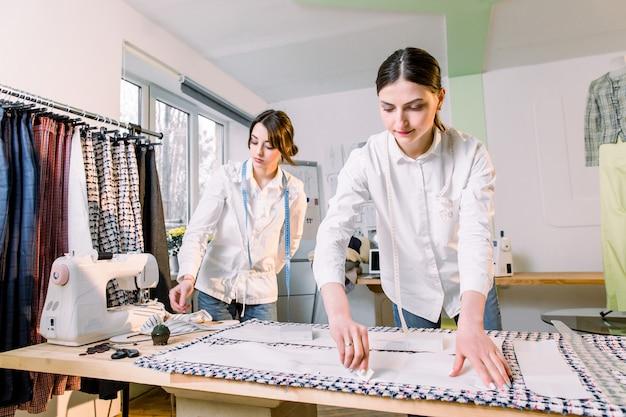 Талия вверх портрет двух молодых красивых портных, работающих с узорами одежды на ткани при пошиве классических брюк в ателье, копией пространства