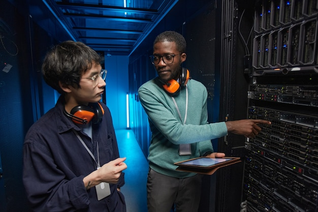 Портрет двух молодых техников, настраивающих серверную сеть во время работы в центре обработки данных