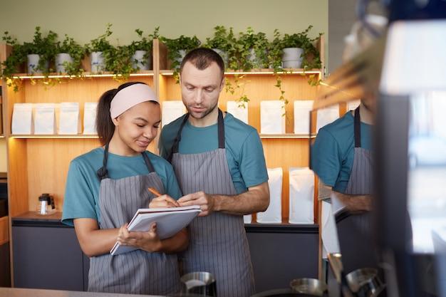Портрет двух молодых официантов в фартуках с буфером обмена, занимающихся инвентаризацией в кафе или кафе, с копией пространства