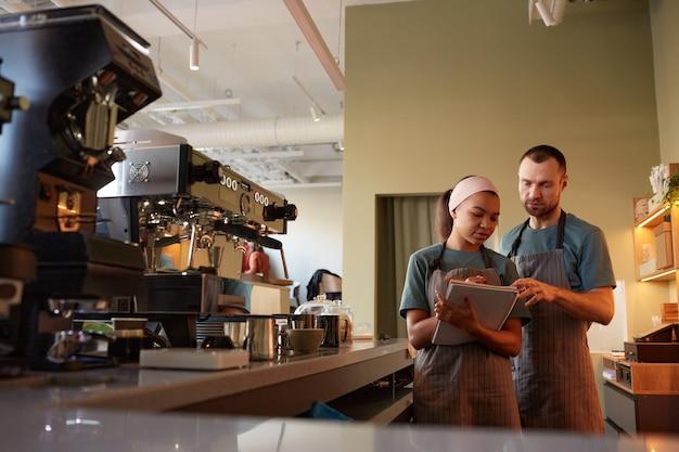 Портрет двух молодых официантов в фартуках, занимающихся инвентаризацией в кафе или кафе, с копией пространства