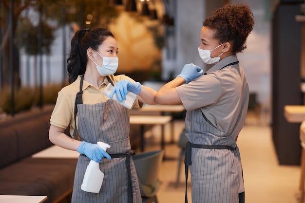 카페에서 일하는 동안 비접촉 인사로 팔꿈치를 부딪치는 두 젊은 여성의 허리 초상화, 코비드 안전 개념, 복사 공간