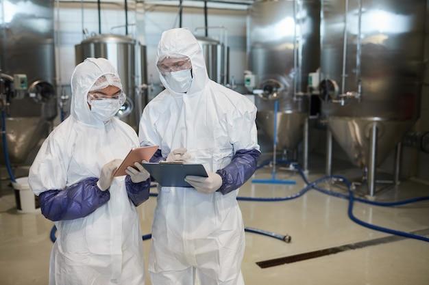 화학 공장에서 디지털 태블릿을 사용하는 동안 방호복을 입은 두 젊은 노동자의 허리 초상화, 복사 공간