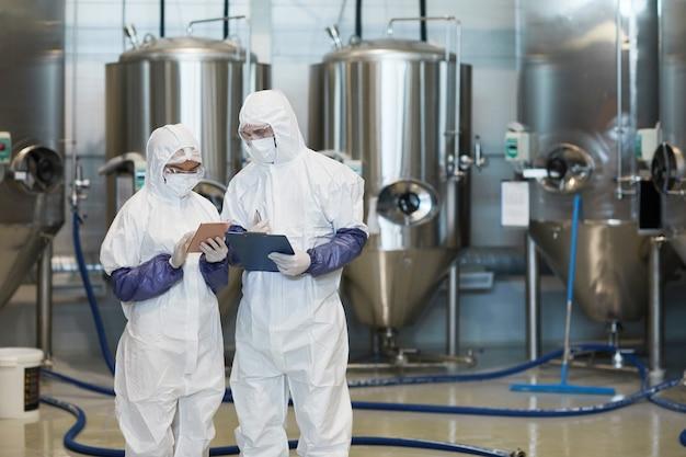 현대 화학 공장에서 디지털 태블릿을 사용하는 동안 방호복을 입은 두 젊은 근로자의 허리 초상화, 복사 공간