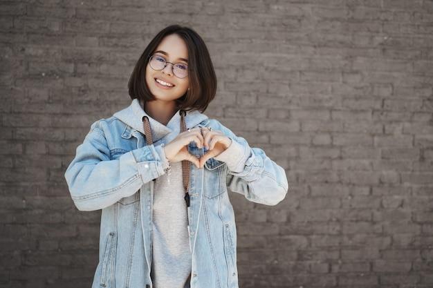 Вытянутый вверх портрет женщины, стоящей снаружи в солнечный весенний день над стеной кирпичного здания, улыбаясь счастливой камерой, показывает знак сердца над грудью, чтобы выразить любовь, заботу и сочувствие.