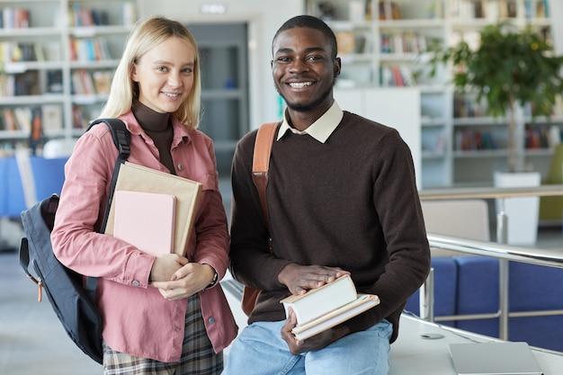 大学図書館に立っている間、若いアフリカ系アメリカ人男性と笑顔の若い女性の肖像画を腰に当てる