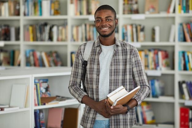 Поднимите талию портрет молодого афроамериканца в школьной библиотеке, держа книги и счастливо улыбаясь в камеру