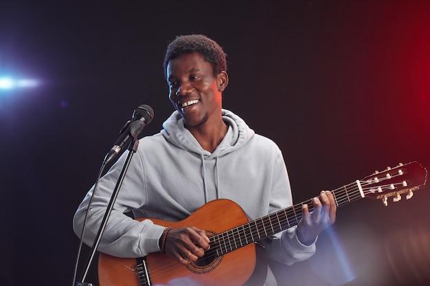 Подняв талию портрет молодого афроамериканца, играющего на гитаре на сцене и поющего в микрофон в свете, копией пространства