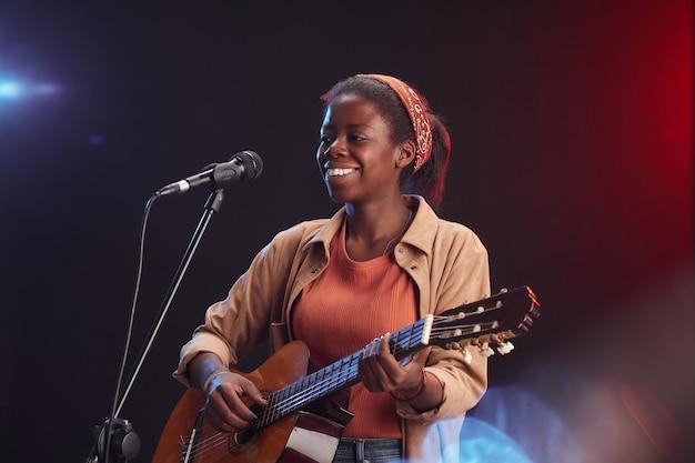 Портрет молодой афро-американской женщины, играющей на гитаре на сцене и поющей в микрофон, улыбается, копией пространства