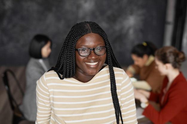 Талия вверх портрет молодой афро-американской женщины, улыбающейся в камеру в офисе с разнообразной группой деловых людей, встречающихся в фоновом режиме, копией пространства