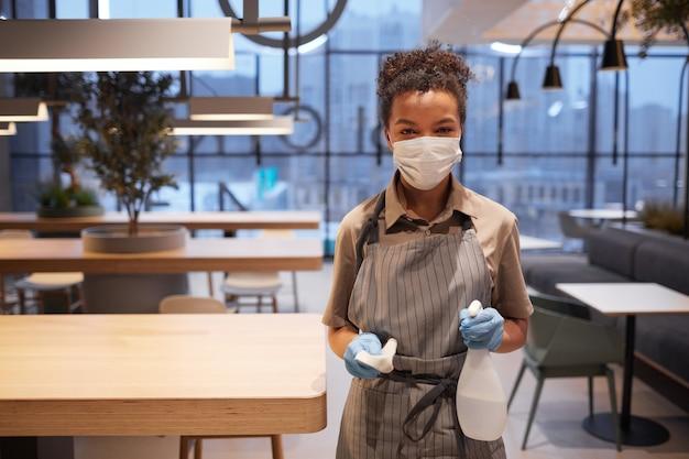 ショッピングモール、コピースペースのフードコートに立っている間、マスクを着用し、カメラを見ている若いアフリカ系アメリカ人労働者の肖像画を腰に当てる