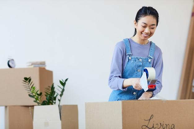 新しい家に引っ越すことに興奮して、テープで段ボール箱を詰めて、幸せそうに笑っている若いアジアの女性の肖像画を腰に当てる