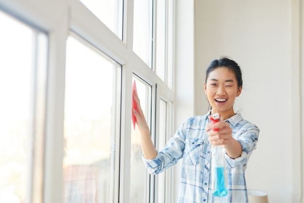 Талия вверх портрет молодой азиатской женщины указывая пульверизатор, мыть окна и наслаждаясь весенней уборкой