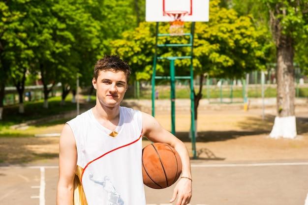 백보드와 그물이 배경에 있는 무성한 녹색 공원에서 팔 아래에 공을 들고 농구 코트에 서 있는 젊은 운동 남자의 허리 위로 초상화